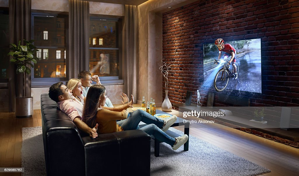 Couples watching very realistic Cycle competition on TV : Stock Photo