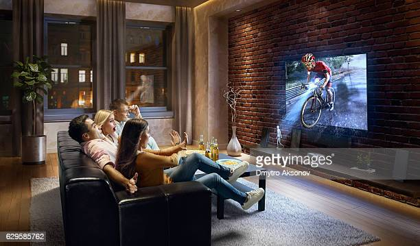 couples watching very realistic cycle competition on tv - arte cultura y espectáculos fotografías e imágenes de stock