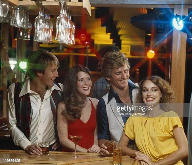 Le coppie con drink presso il nightclub sorridente