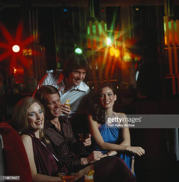 Couples with drink at nightclub, smiling