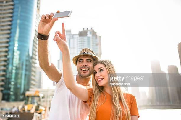 coupletake a selfie against the skyline of dubai marina