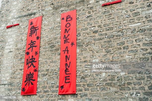 Couplets in with Chinese and Western scripts hanging on brick wall