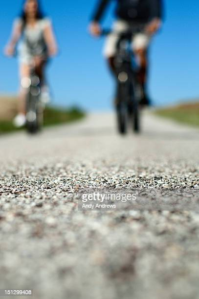 A couplke on bikes, cycling on a country road