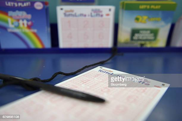 A coupon for Tatts Group Ltd's TattsLotto lottery game is arranged for a photograph at a newsagent's store in Melbourne Australia on Thursday Dec 15...