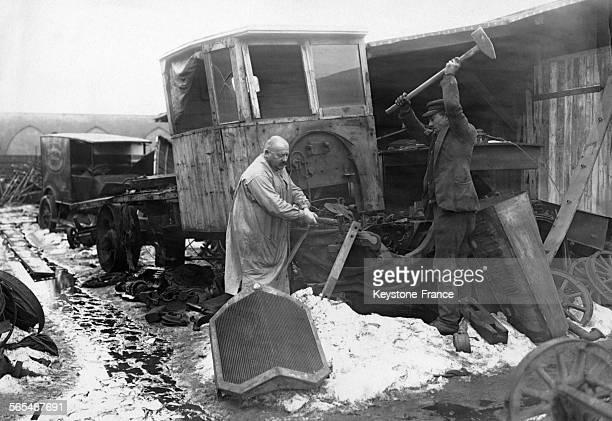 A coups de masse deux ouvriers démontent un camion dans la plus grande décharge automobile d'Europe à Berlin Allemagne circa 1930
