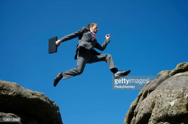 Courageous Businessman Jumping Between Rocks Against Blue Sky