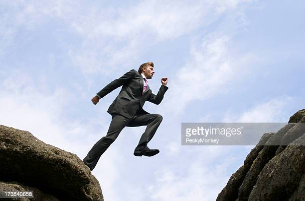 Courageous Businessman Jumping Over Rock Chasm