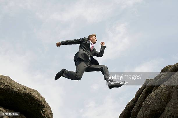 Courageous Businessman Leaping between Rocks