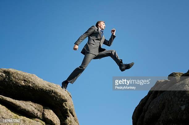 Mutige Geschäftsmann mit gefährlichen Schritt auf das Tal