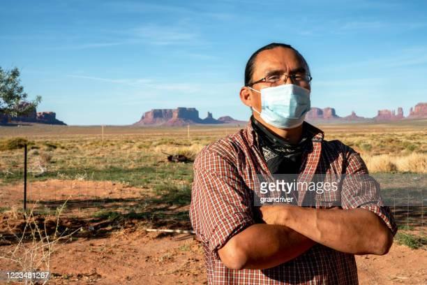 モニュメントバレー部族公園に住む勇敢なナバホの男は、covid19からの保護のためのマスクを着用しています - ナバホ文化 ストックフォトと画像