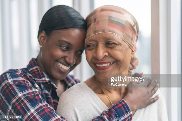 courageous woman with cancer spends precious time with adult daughter - cancer illness stock pictures, royalty-free photos & images