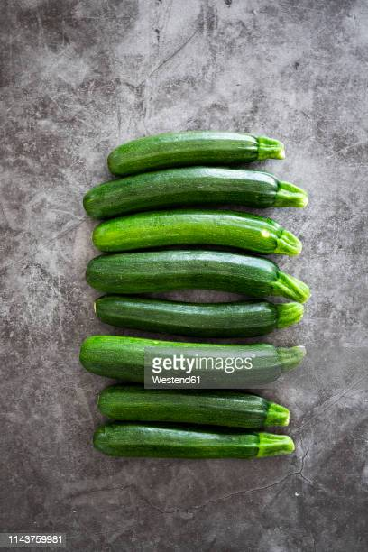 courgettes in a row, grey background - zucchini stock pictures, royalty-free photos & images