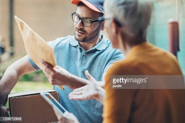 courier checking a package before delivery - carteiro imagens e fotografias de stock