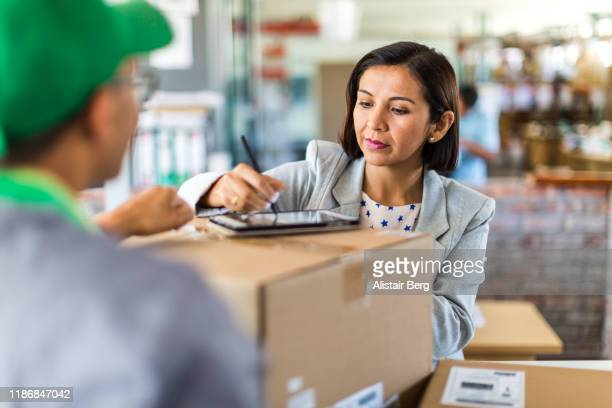 courier collecting or delivering parcels from small business - sending stock pictures, royalty-free photos & images