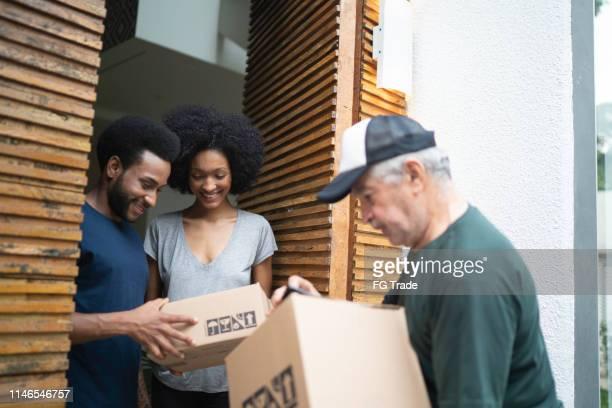 correio que entrega caixas a um par novo - receber - fotografias e filmes do acervo