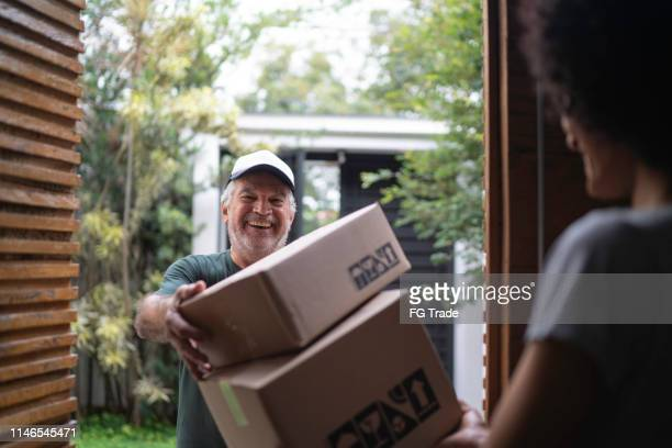 courier delivering boxes to a young woman - receiving stock pictures, royalty-free photos & images