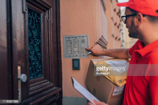 courier delivering packages - ringing doorbell stock pictures, royalty-free photos & images