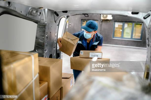 courier delivering parcel - postal worker stock pictures, royalty-free photos & images