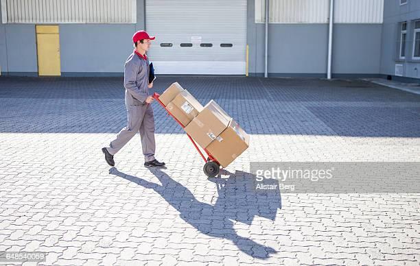 courier delivering parcels and boxes - empurrar atividade física imagens e fotografias de stock