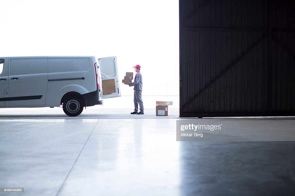 Courier delivering parcels and boxes : Stock Photo