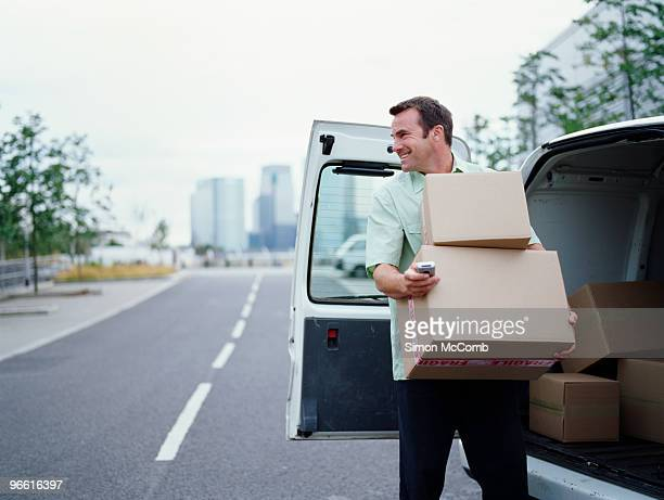 a courier delivering parcels - van stock pictures, royalty-free photos & images