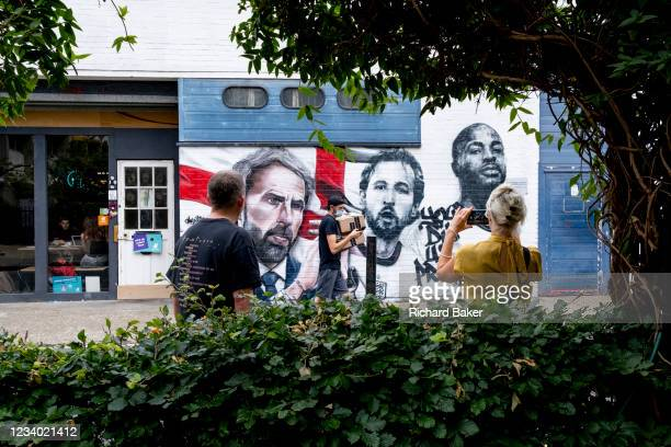 Courier delivers packages and onlookers admire the mural featuring England football manager Gareth Southgate, captain Harry Kane and Raheem Sterling...