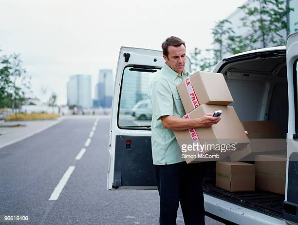 a courier delivers parcels - loader reading stock pictures, royalty-free photos & images