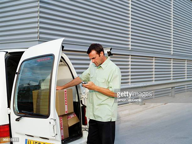 a courier delivers parcels. - loader reading stock pictures, royalty-free photos & images