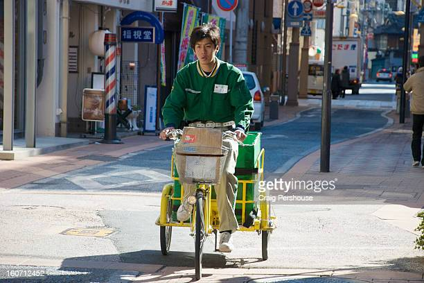 Courier doing his deliveries by bicycle cart