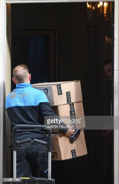 A DPD courier driver carries Amazon Prime branded boxes into 10 Downing Street in central London on April 14 2020 The British government warned...
