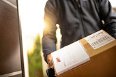 Courier holding cardboard box for delivery
