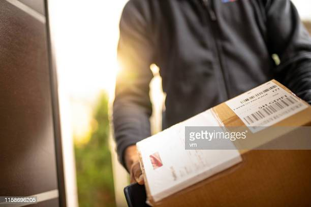 courier holding cardboard box for delivery - delivery person stock pictures, royalty-free photos & images