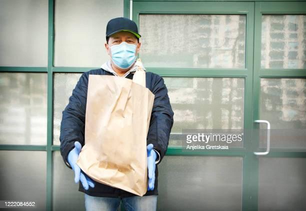 courier in protective mask and medical gloves delivers takeaway food. delivery service under quarantine, disease outbreak, coronavirus covid-19 pandemic conditions. - essenzielle berufe und dienstleistungen stock-fotos und bilder