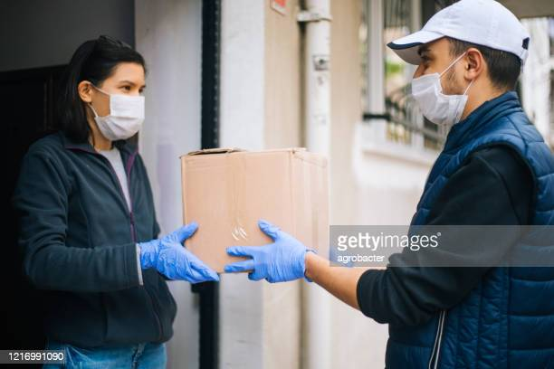 courier in protective mask delivers parcel to client - essential workers stock pictures, royalty-free photos & images