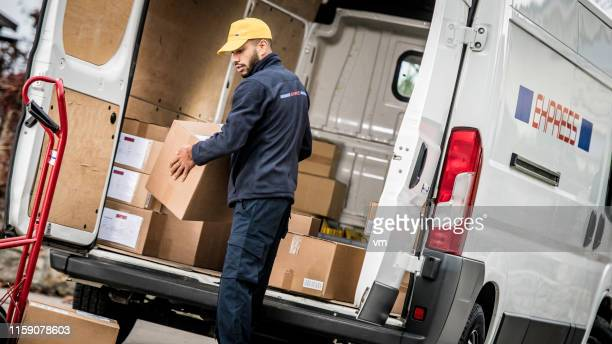 courier loading boxes on a push cart - commercial land vehicle stock pictures, royalty-free photos & images