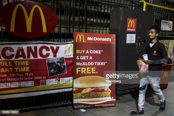 A courier of Swiggy a food ordering and delivery service operated by Bundl Technologies Pvt walks past menu items advertised outside a McDonald's...