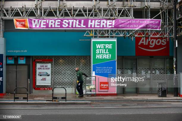 A courier pulls a crate of milk cartons past a shuttered Argos catalog shop operated by J Sainsbury Plc in London UK on Friday June 12 2020 The UK...