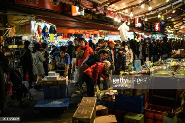 A courier pushes goods on a trolley as visitors browse stalls and others pass through Ameya Yokocho market on January 4 2018 in Tokyo Japan Ameya...