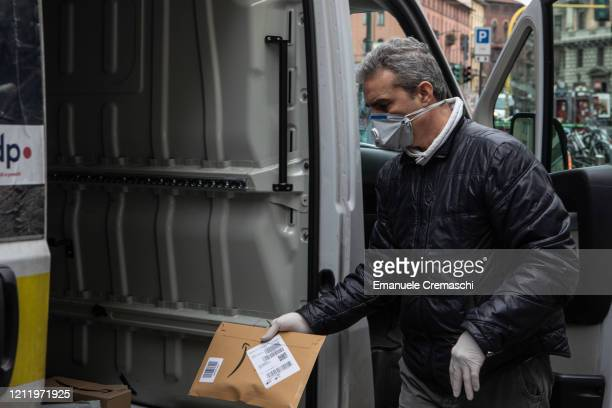 Courier, wearing a respiratory mask, handles an Amazon parcel on March 11, 2020 in Milan, Italy. The Italian Government has strengthened up its...
