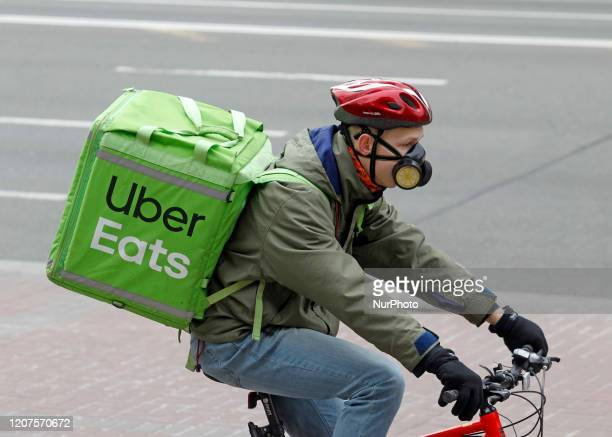 Courier with Uber Eats bag rides on a bike in Kyiv, Ukraine, on 17 March, 2020. To stem the spread of the coronavirus COVID-19 from March 18, Ukraine...