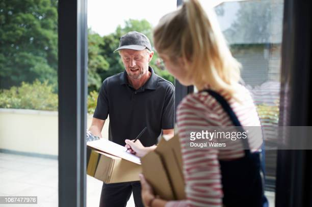 courier worker delivering parcel to woman. - receiving stock pictures, royalty-free photos & images