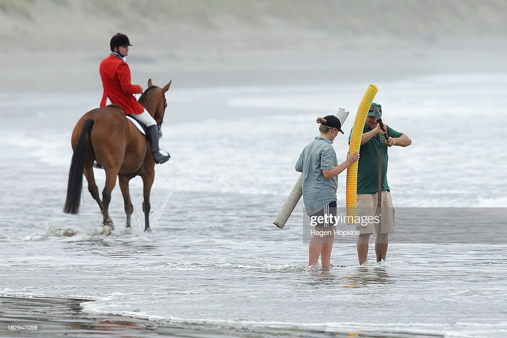Course attendants install a marker during the Castlepoint Beach Races at Castlepoint Beach on March 2, 2013 in Masterton, New Zealand.