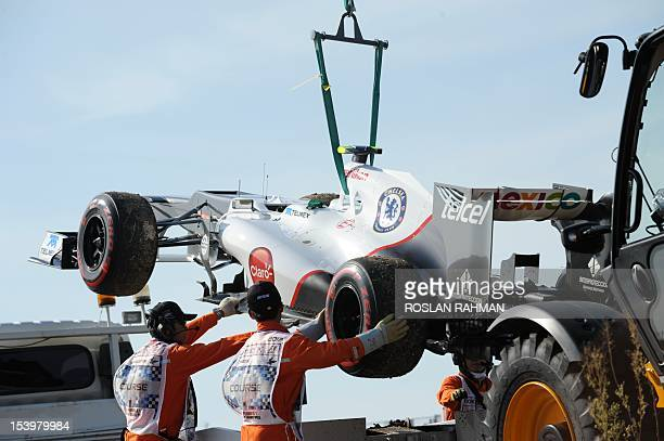 Course crews remove Sauber's driver Sergio Perez of Mexico race car after it suffered engine problems during the second practice session of the...