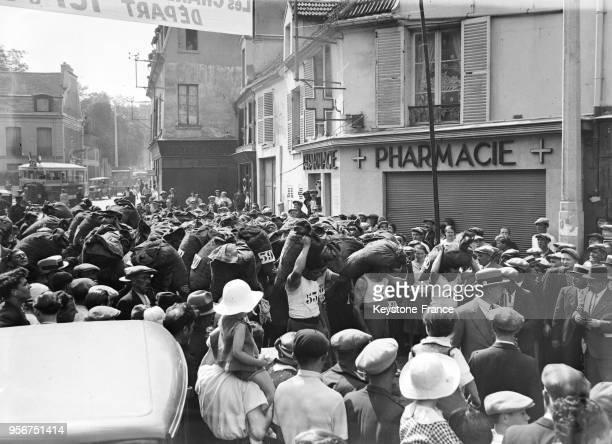 Course des charbonniers portant un sac d'anthracites sur le dos la foule acclamme les participants à Nanterre France en 1935