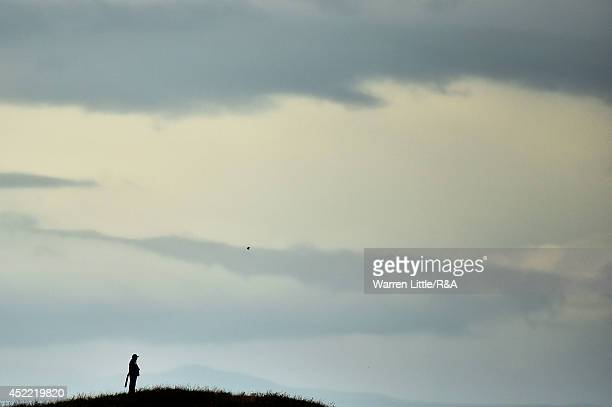 A course marshall stands atop a hill during a practice round prior to the start of the 143rd Open Championship at Royal Liverpool on July 16 2014 in...