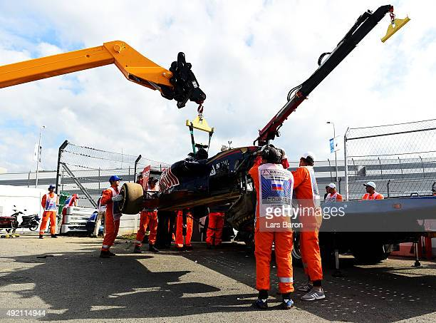 Course marshalls remove Carlos Sainz of Spain and Scuderia Toro Rosso's damaged car after he crashed during final practice for the Formula One Grand...