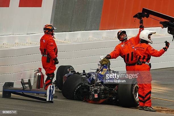 Course officials clear the wreckage of Mike Conway's #24 Dreyer Reinbold Racing Dallara Honda after he hit the wall in turn four during the IndyCar...