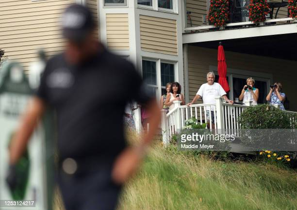Course residents watch as Phil Mickelson of the United States walks on the 18th hole during the final round of the Travelers Championship at TPC...