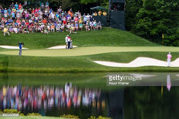 Course scenic view as fans watch Justin Thomas hit out of a greenside bunker on the 12th hole green during the final round of the Memorial Tournament...