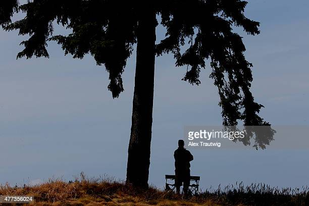A course volunteer watches play during a practice round prior to the start of the 115th US Open Championship at Chambers Bay on June 16 2015 in...